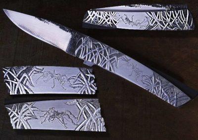 Le 414, liner lock, lame en sand-inox coeur acier 135C3 flancs en inox, plaquettes en Z20C13 gravées en font creux, ciselées, gravées avec la technique du bulino..