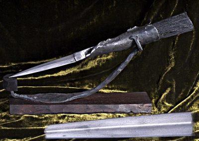 Objet de bureau d'inspiration celte, forgé d'une seul pièce dans un lingot d'acier antique, manche en morta, support en acier antique et palissandre.