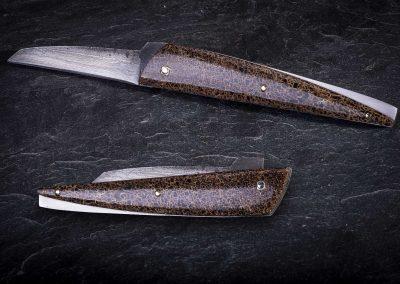 Le Ds, cran plat, lame en damas multicouches tiré de long au panier 2500, platines décaissées et bouchonnées, plaquettes en os d mammouth stabilisé.1360€ Vendu.