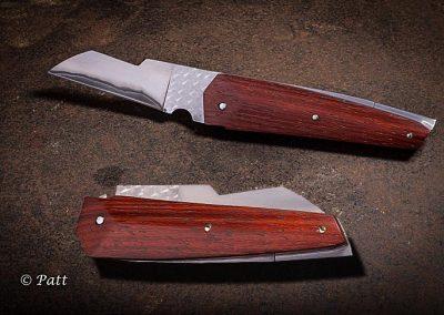 Le Krystal, couteau à système pompe arrière, la lame est en sand-inox, coeur en acier 135C3 flancs en inox, elle est bouchonnée sur la partie entablure. Les platines sont décaissées et bouchonnés, les plaquettes sont en paddock travaillées sur trois angles.