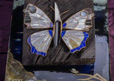 Le Papillon, le couteau est en jais avec une lame en acier damas multi-barreaux, à système pompe arrière, il fait 14cm ouvert. Il est posé sur une silhouette de papillon, en argent dorée à l'or fin. Les ailes sont réalisées en nacre blanche, nacre jaune, nacre noire et lapis lazuli. Les ailes sont amovibles et sont posées sur un socle de Couëron âgé de 8000ans, celui-ci repose sur une laque faite de feuilles d'or et de poudre de nacre.