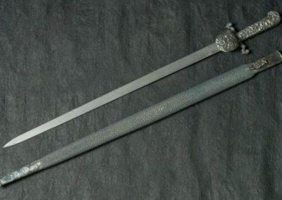 Épée 85cm, lame en acier damas multicouches, ornementations en argent patiné, fourreau en galuchat.