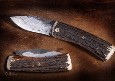 Le Manu, système à cran forcé, lame en sandwich vieux fer, coeur acier 135C3 flancs en vieux fer daté de 1900, manche en bois de cerf sambar.Vendu 550€.