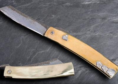 Pattogami, lame en sandwich vieux fer, coeur acier 135C3 flancs en vieux fer , manche en laiton décoré d'une scènette en argent. 420€.